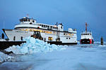 As a pile of ice chunks lays beside the dock, fished out with backhoe, the Emerald Isle nudges herself into the birth.